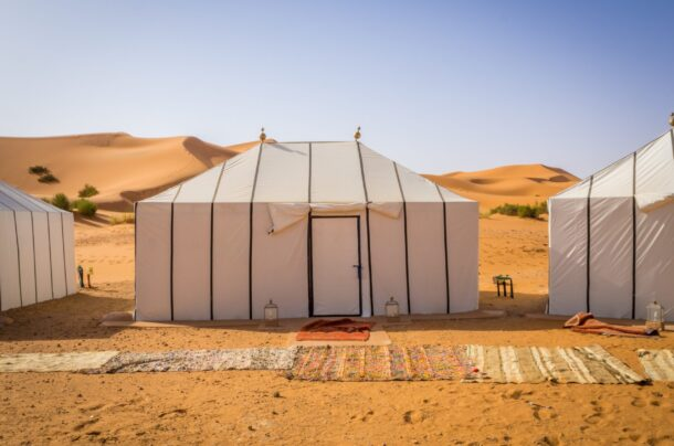 The white Berber tents in the Sahara Desert, Morocco with carpets on the sandy ground